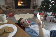 Young man relaxing, using digital tablet on floor near fireplace in Christmas living room - HEROF16353