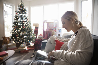Woman relaxing, drinking coffee and using digital tablet in Christmas living room - HEROF16365