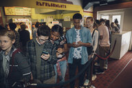 Tween boys and and girls texting with smart phones waiting in queue in movie theater lobby - HEROF16368