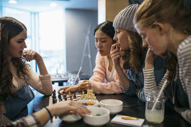 Tween girl friends playing chess and eating candy at cafe table - HEROF16377