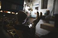 Tween boy projectionist texting with smart phone in dark movie theater - HEROF16383