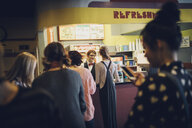 Tweens waiting in queue at refreshments concession stand in movie theater - HEROF16386