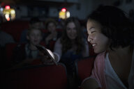 Tween girls texting with smart phone in dark movie theater - HEROF16389