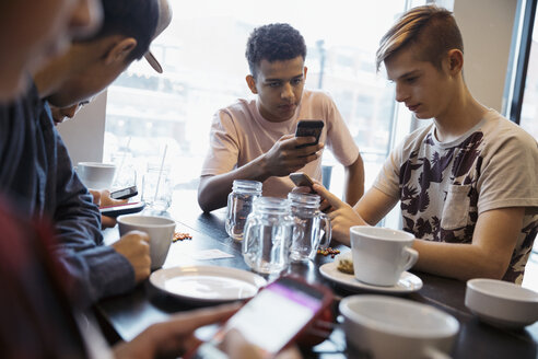 Tween boy friends texting with smart phones at cafe table - HEROF16407