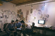 Tattoo artists brainstorming with digital tablet in tattoo studio office - HEROF16419