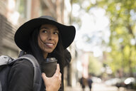 Smiling young woman in hat drinking coffee on street - HEROF16476
