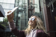 Smiling blonde young woman in sunglasses taking selfie with camera phone - HEROF16479