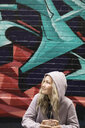 Smiling young woman in hoody looking up along graffiti wall - HEROF16482