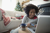 Smiling woman with credit card online Christmas shopping at laptop in living room - HEROF16488
