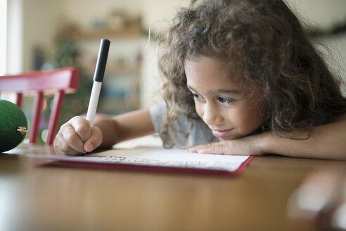 Smiling girl writing Christmas letter to Santa at table - HEROF16500