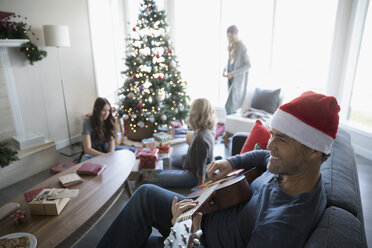 Smiling father in Santa hat playing guitar while family wraps gifts in living room with Christmas tree - HEROF16566