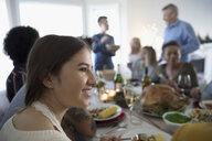 Smiling teenage girl enjoying turkey Christmas dinner with family at table - HEROF16569