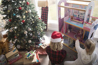 Sisters playing with dollhouse next to Christmas tree in living room - HEROF16578
