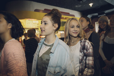 Smiling tween girls waiting in queue in movie theater lobby - HEROF16590