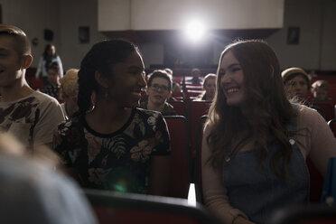 Smiling tween girl friends watching movie in dark movie theater - HEROF16599