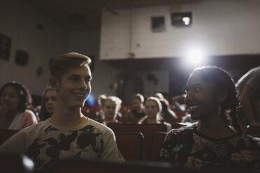 Smiling tween couple watching movie in dark movie theater - HEROF16602