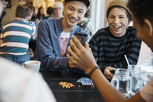 Smiling tween boy friends texting with smart phone at cafe table - HEROF16614