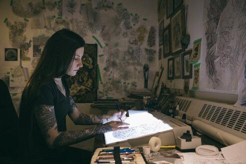 Tattoo artist sketching on light table in dark tattoo studio office - HEROF16617
