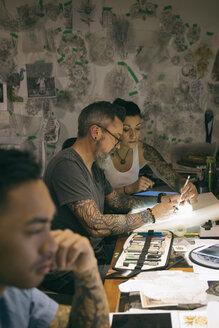 Tattoo artist brainstorming, sketching at light table in tattoo studio office - HEROF16629