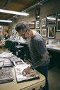 Tattoo artist reviewing sketchbooks in tattoo studio - HEROF16632