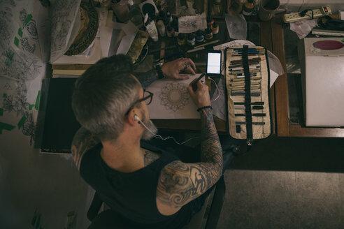 Tattoo artist sketching at table - HEROF16635