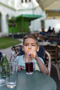 Little boy drinking soft drink with a straw - MOMF00620