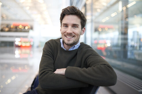 Portrait of smiling young businessman sitting in waiting area - PNEF01219