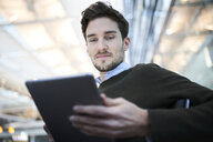 Smiling young businessman using tablet - PNEF01222