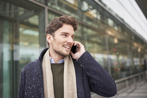 Smiling young businessman on cell phone in snow - PNEF01225