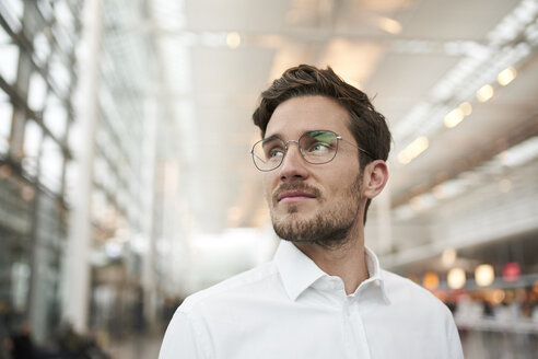 Portrait of young businessman wearing glasses looking around - PNEF01246