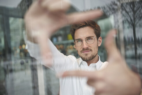 Portrait of young businessman behind glass pane shaping a finger frame - PNEF01249