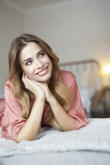 Smiling young woman in dressing gown lying in bed - PNEF01267