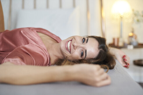 Portrait of happy young woman in dressing gown lying in bed - PNEF01273