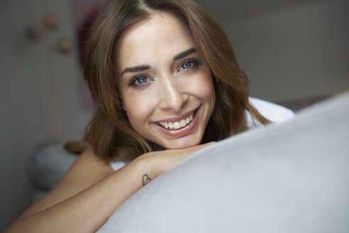 Portrait of smiling young woman on couch - PNEF01285