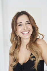 Portrait of happy young woman wearing black dress - PNEF01291