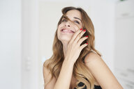 Happy young woman playing with her hair - PNEF01294