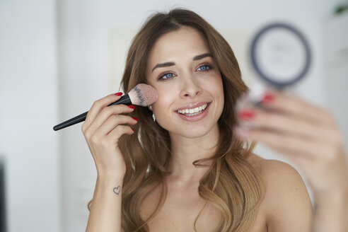 Smiling young woman applying make-up - PNEF01297