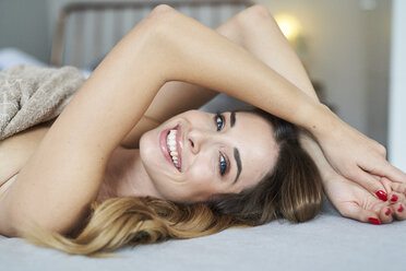 Portrait of happy young woman lying in bed - PNEF01303