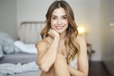 Portrait of smiling young woman sitting on bed - PNEF01306