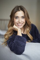 Portrait of smiling young woman on couch - PNEF01309