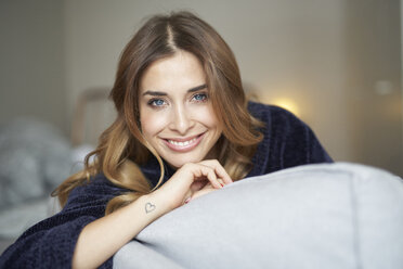 Portrait of smiling young woman on couch - PNEF01312