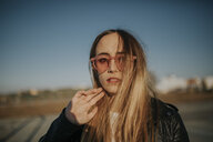 Portrait of long-haired young woman wearing sunglasses outdoors - DMGF00008