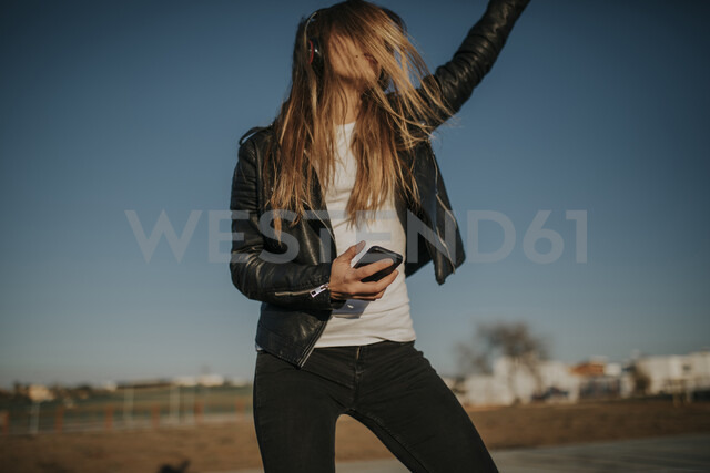 Happy young woman listening music with headphones outdoors - DMGF00017 - David Molina Grande/Westend61