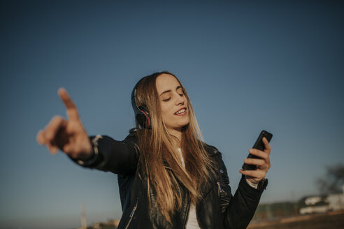 Happy young woman listening music with headphones outdoors - DMGF00020
