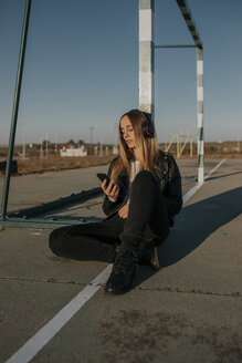 Pozoblanco, Cordoba, Spain, Sitting urban girl listening music with headphones, youth culture - DMGF00023