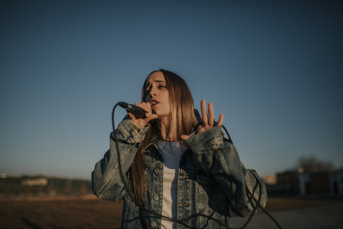 Young woman singing with a microphone outdoors - DMGF00038