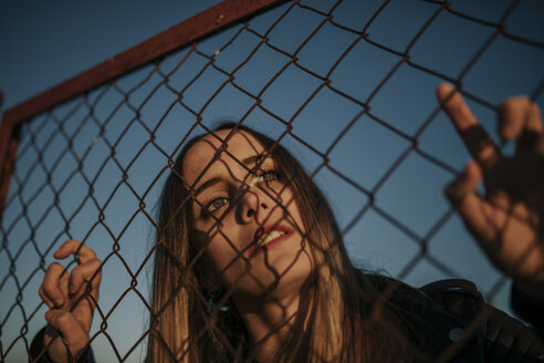 Pozoblanco, Cordoba, Spain, Urban girl looking through a fence, youth culture - DMGF00044