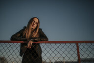 Portrait of young woman leaning on wire mesh fence - DMGF00047