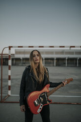 Portrait of cool young woman with guitar on sports field - DMGF00053