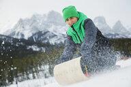 Boy sledding in snowy field - HEROF16745